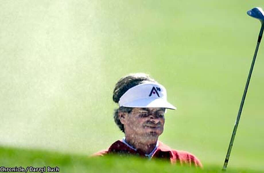 Fred Couples squints as sand blows into his eyes after hitting a sand shot on the 14th hole of Pebble Beach Golf Links during the AT&T Pebble Beach National Pro-Am third round. Chronicle photo by Darryl Bush Photo: Darryl Bush