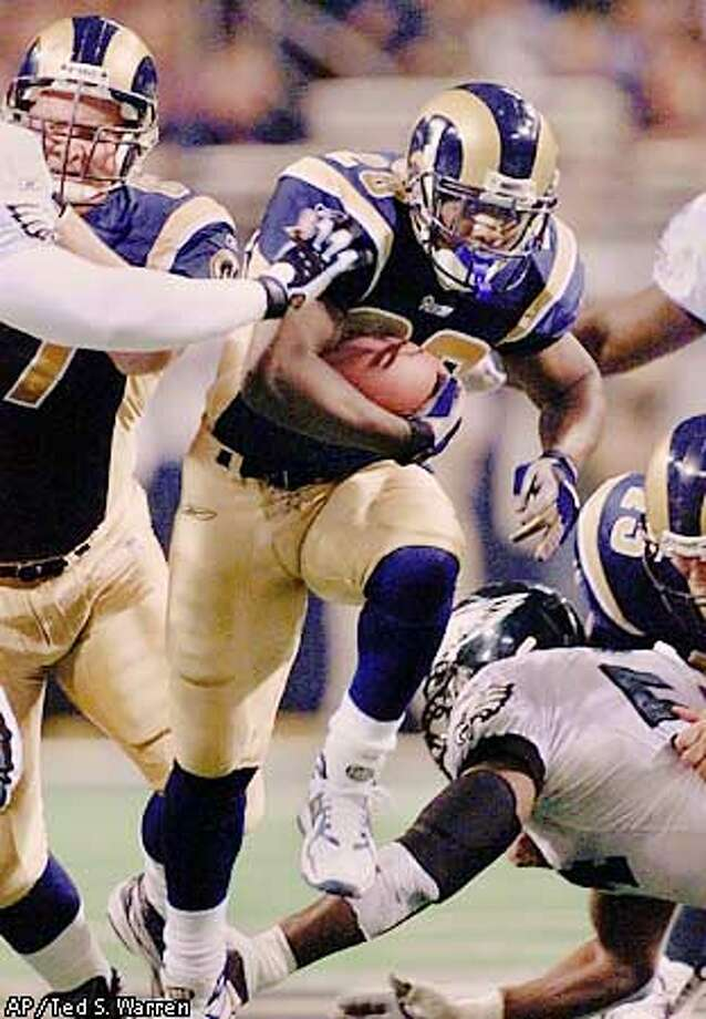 St. Louis Rams running back Marshall Faulk (28) runs up the middle against the Philadelphia Eagles defense during the second qaurter of the game in St. Louis, Sunday, Jan. 27, 2002. (AP Photo/Ted S. Warren) Photo: TED S. WARREN