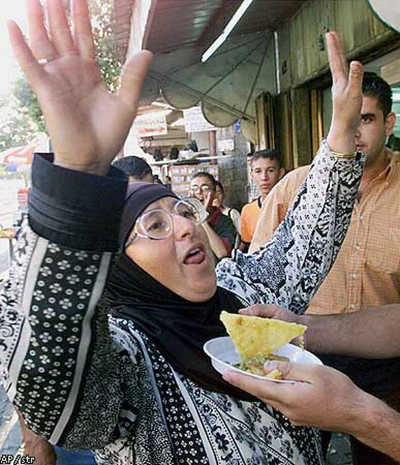 A Palestinian woman receives free sweets from a vendor as groups of locals in east Jerusalem's Old City celebrate after hearing the news of a terrorist attack on the World Trade Center in New York, Tuesday, Sept. 11, 2001. (AP Photo/str) Photo: STR
