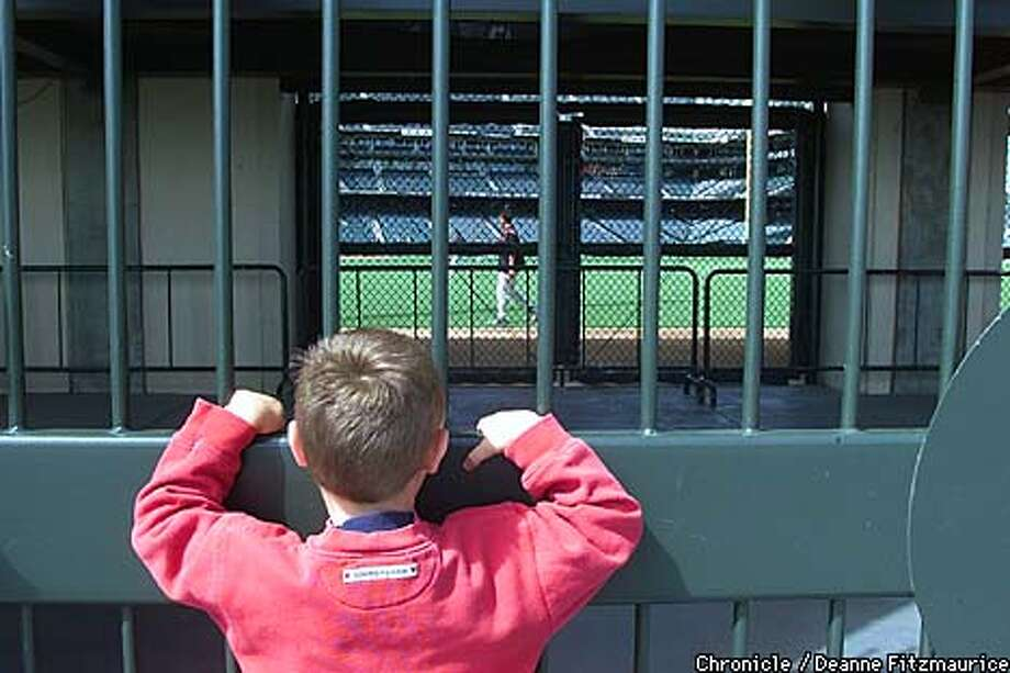 Jimmy McCarthy, 4, from Danville watches the SF Giants workout through the gates on the rightfield side of Pacific Bell Park on a weekend when sports are suspended due to the terrorist tragedy on the World Trade Center and the Pentagon.  CHRONICLE PHOTO BY DEANNE FITZMAURICE Photo: DEANNE FITZMAURICE