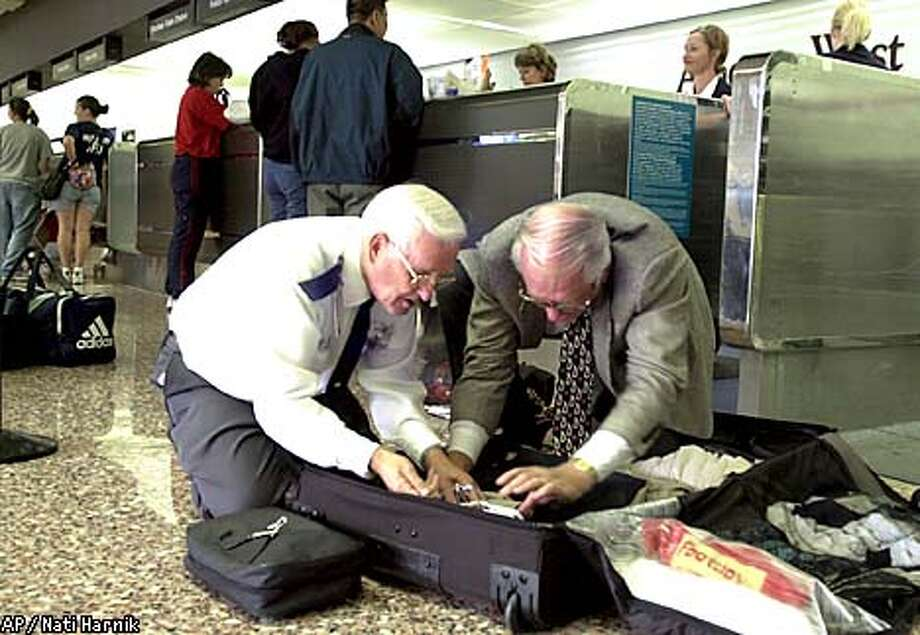 Alan Skuba of Palm Desert, Calif., right, helps an unidentified security guard at Eppley Airfield in Omaha, Neb., search his baggage prior to boarding a flight, Thursday Sept 13, 2001, as part of new stricter security measures implemented in U.S airports. After long waits and uncertainty, some of the hundreds of air travelers stranded in Nebraska began boarding planes Thursday.(AP Photo/Nati Harnik) Photo: NATI HARNIK