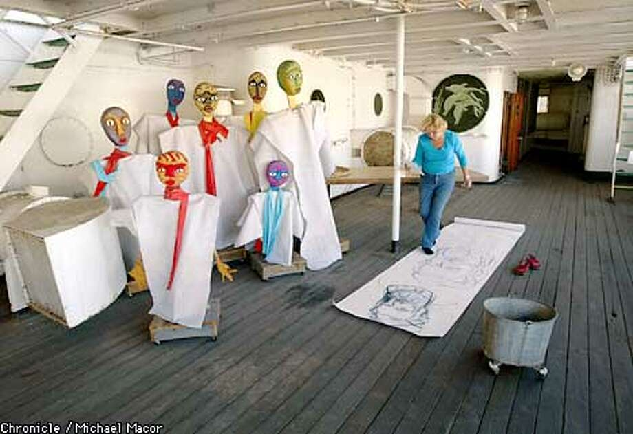 Artist Jasna Slebinger inspects sketches she is making on the Artship deck under the gaze of puppets made by artist Deborah Kaupman. Chronicle photo by Michael Macor
