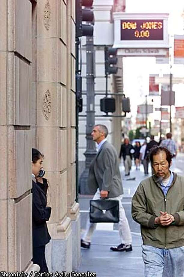 San Francisco financial district regulars walk through nearly-empty streets under the Charles Schwab building, where the stock display shows no movement on the Dow Jones Industrial Index on Tuesday, September 11, 2001, the same morning of the worst terrorist attack in U.S. history in New York, and Washington, D.C. (Photo by Carlos Avila Gonzalez/The San Francisco Chronicle) Photo: CARLOS AVILA GONZALEZ