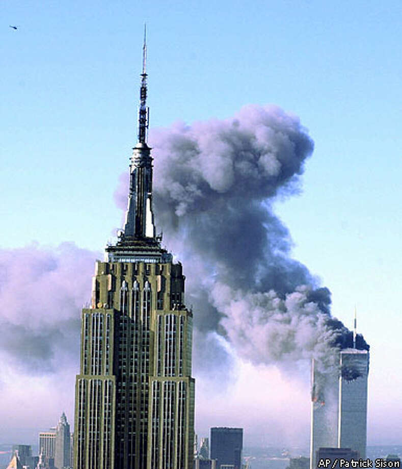 Plumes of smoke poured from the World Trade Center buildings in New York after planes crashed                      into the upper floors of both towers. The Empire State building is seen in the foreground. Associated Press photo by Patrick Sison
