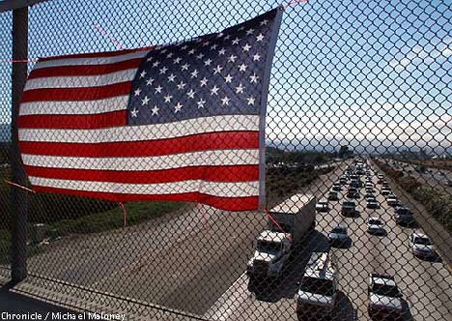 Someone attached an American flag to the fence on the Santa Rita Road overcrossing to I580 in Pleasanton. It faced the oncoming afternoon commute traffic.  CHRONICLE PHOTO BY MICHAEL MALONEY Photo: MICHAEL MALONEY