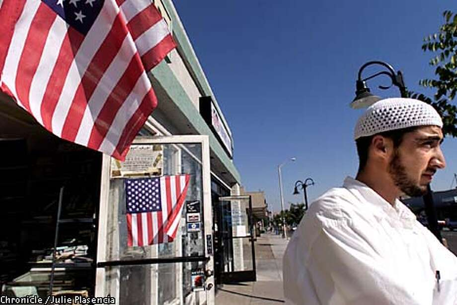 "Said Yousef, 22, dressed in his usual clothing to identify himself as a Muslim waits for a friend outside Pamir Food Mart in Freemont. The market is one of a dozen stores and restaurants that make up a three block area community members call ""little Kabul"" and that caters to the Afghan community living in the Freemont area.  (JULIE PLASENCIA/THE CHRONICLE) Photo: JULIE PLASENCIA"