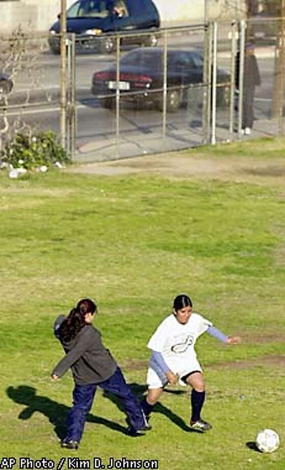 Students on the Huntington Park High School girls soccer team practice Thursday, Jan. 31, 2002 on one of the school's fields next to a busy street in Huntington Park, Calif. In California's smoggiest communities, the most athletic children are three times more likely than their couch-potato peers to get asthma, University of Southern California researchers have concluded. (AP Photo/Kim D. Johnson) Photo: KIM D. JOHNSON