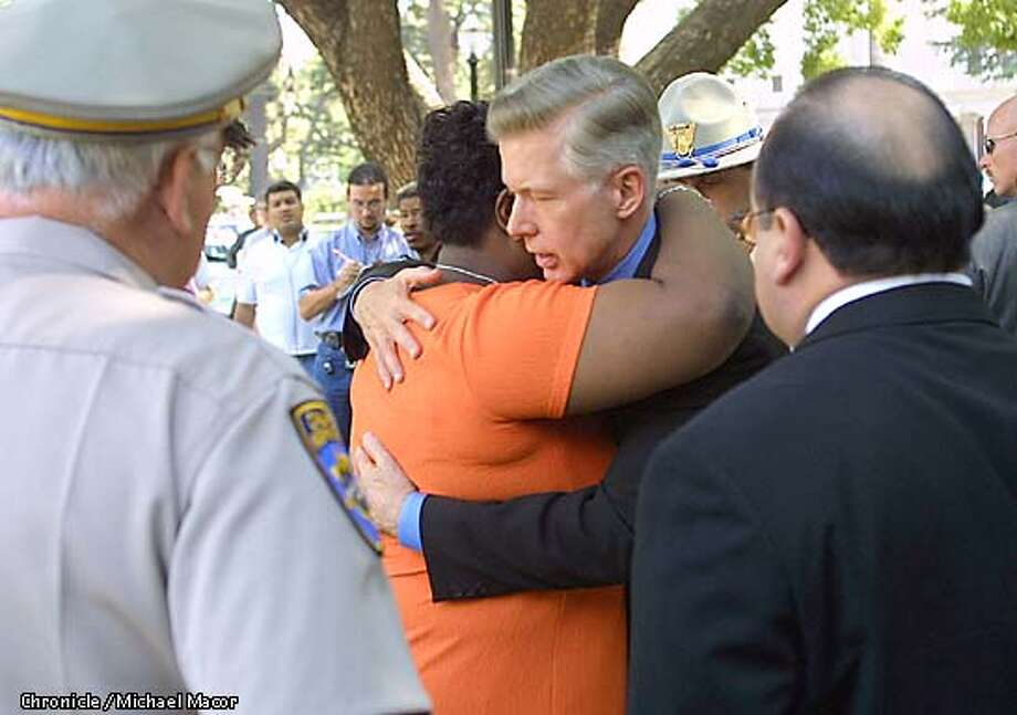 Governor Davis greets and hugs a State employee (didn't want her name used) who lost a relative in the New York Bombings. Flanked by CHP Commissioner Dwight Helmick, back left and Lt. Governor Cruz Bustamante, back right. Governor Davis announces the creation of a fund to provide monetary assistance to the families of fallen peace officers in New York City. by Michael Macor/The Chronicle Photo: MICHAEL MACOR