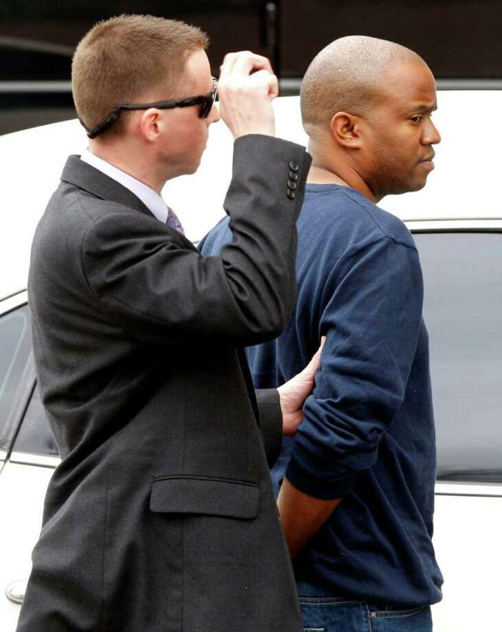 FBI agents take Gemase Lee Simmons (right) to federal court in San Antonio on Jan. 31, 2012, after he was arrested on federal child-porn related charges. Simmons was featured in a news segment on Dateline alleging he scammed several youths into believing they were being filmed for a reality show about modeling. Photo: William Luther, San Antonio Express-News / © 2012 SAN ANTONIO EXPRESS-NEWS