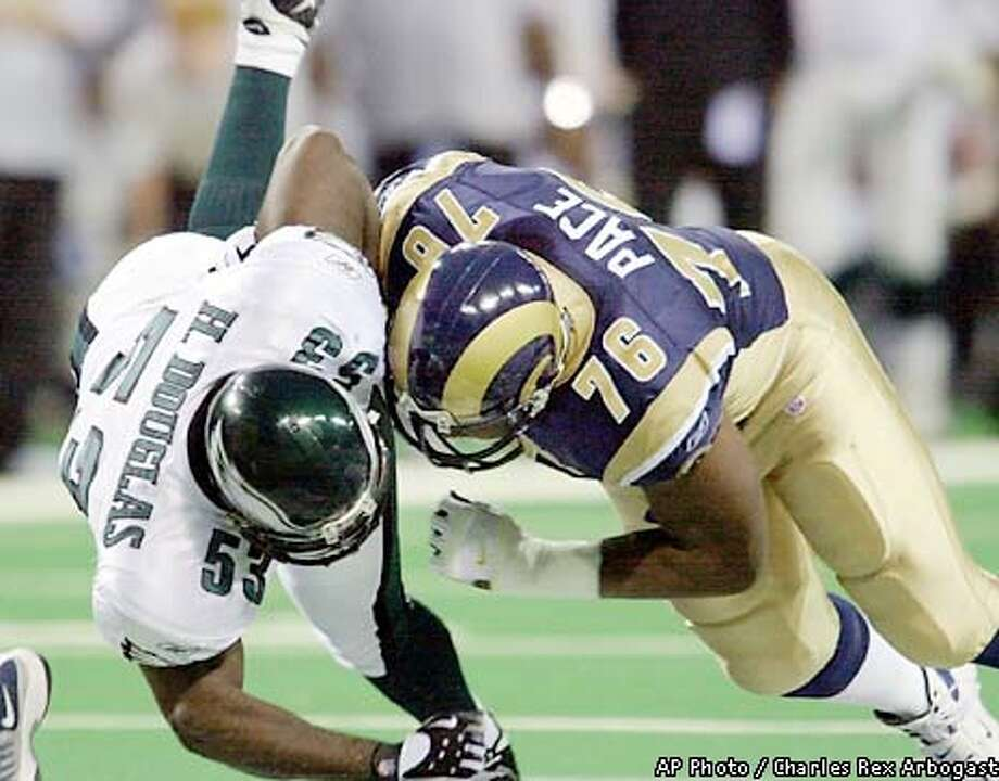 Philadelphia Eagles linebacker Hugh Douglas (53) is knocked over by St. Louis Rams tackle Orlando Pace (76) in the first half of the game Sunday, Jan. 27, 2002 in St. Louis. (AP Photo/Charles Rex Arbogast) Photo: CHARLES REX ARBOGAST
