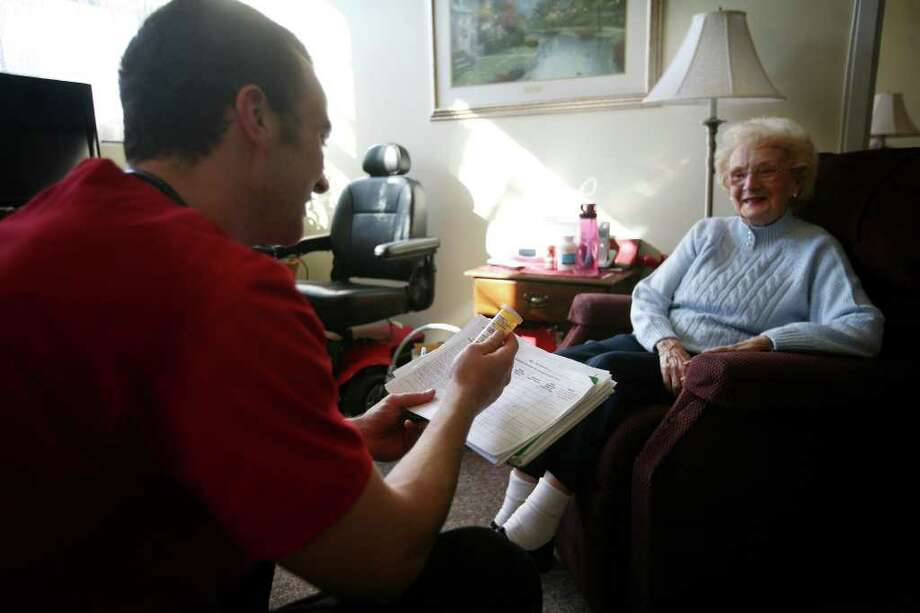 Fairfield University senior nursing student Jim Skane reviews medical information with senior Jean Whalen at Grasmere Eldercare in Fairfield on Tuesday, January 31, 2012. Photo: Brian A. Pounds / Connecticut Post