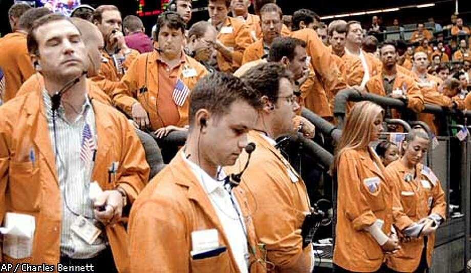 Workers at the Chicago Mercantile Exchange pause for a moment of silence Thursday, Sept. 13, 2001, to recognize the victims and survivors of Tuesday's terrorist attacks. Many traders at the exchange tucked small American flags in their jacket pockets as they returned to the trading floor. Bond trading resumed and futures activity restarted on the Chicago Board of Trade and Chicago Mercantile Exchange.(AP Photo/Charles Bennett) Photo: CHARLES BENNETT