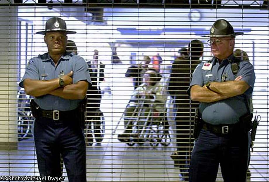 Two Massachusetts State Police troopers stand in front of the closed entrance to American Airlines gate area as passengers are evacuated, rear, at Logan International Airport in Boston, Tuesday, Sept. 11, 2001. American Airlines confirmed two of its planes were hijacked and crashed into the World Trade Center. American said the flights were Flight 11, a Boeing 767 en route from Boston to Los Angeles and Flight 77, a Boeing 757 operating from Washington Dulles to Los Angeles. (AP Photo/Michael Dwyer) Photo: MICHAEL DWYER