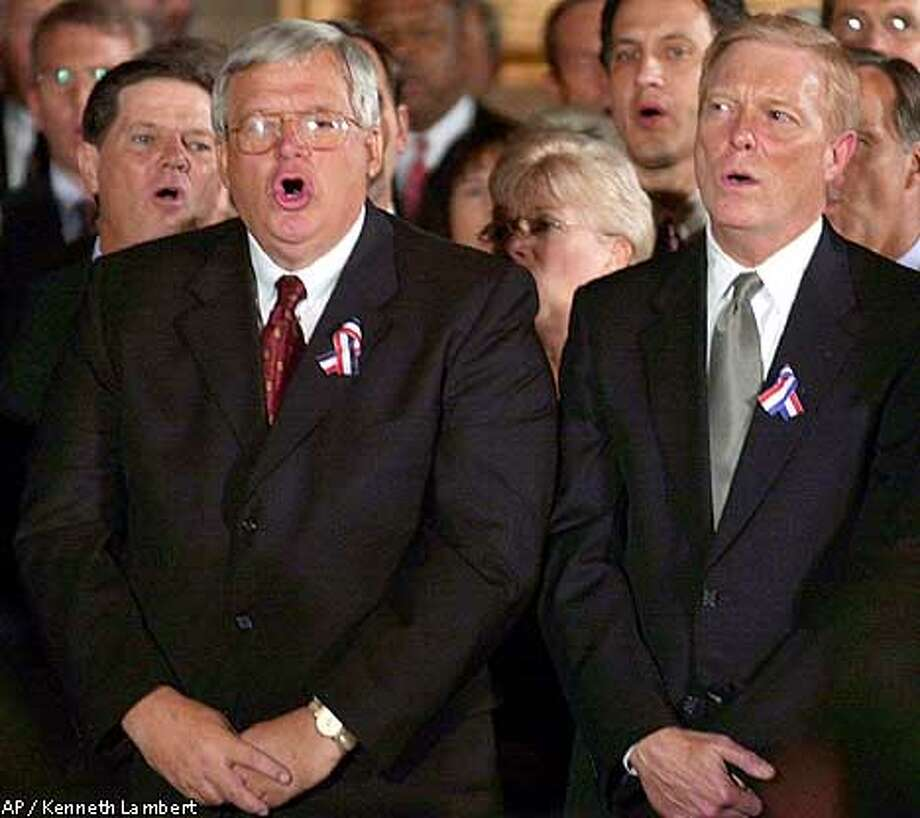 "CORRECTS TITLE OF DELAY FROM HOUSE MAJORITY WHITE TO HOUSE MAJORITY WHIP--From left: Rep. Tom DeLay, R-Texas, house majority whip, House Speaker Dennis Hastert, R-Ill., and Rep. Richard Gephardt, D-Mo., sing ""God Bless America,"" Wednesday, Sept. 12, 2001, during a prayer vigil in the rotunda of the Capitol held in honor of those who died in Tuesday's terrorist acts on the U.S. (AP Photo/Kenneth Lambert) Photo: KENNETH LAMBERT"