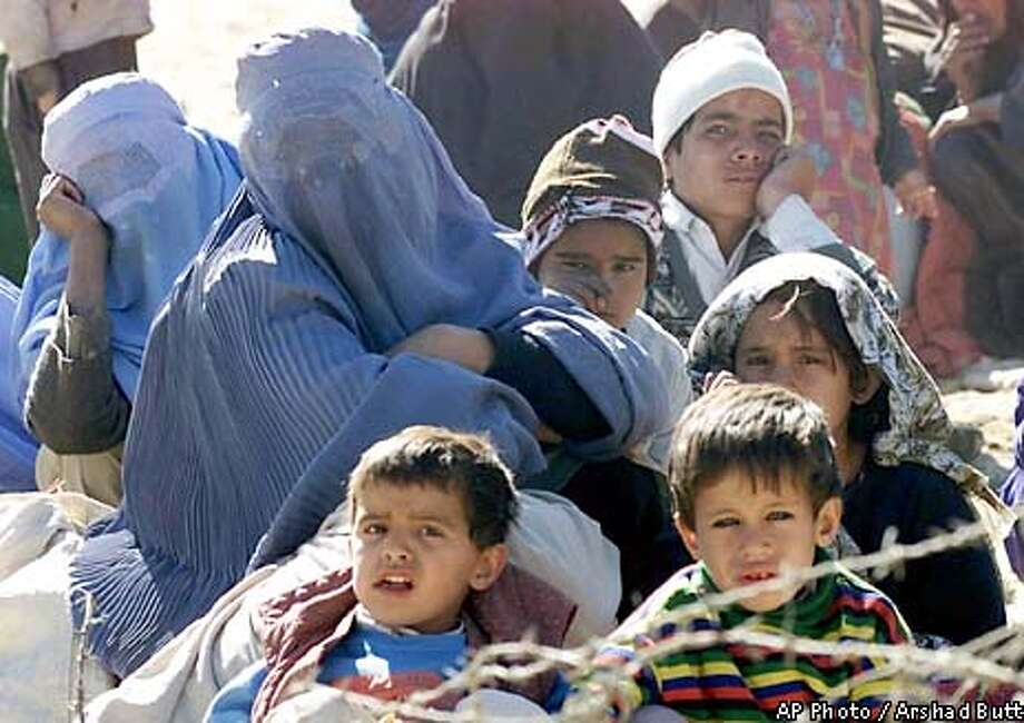 Afghan refugees wait at the Pakistan-Afghanistan border, in Chaman near Quetta, Pakistan for permission to enter Pakistan, Sunday, Jan. 20, 2002. In the last three months, nearly 40,000 new refugees have been registered and housed at three temporary camps a few miles inside Pakistan. (AP Photo/Arshad Butt) Photo: ARSHAD BUTT