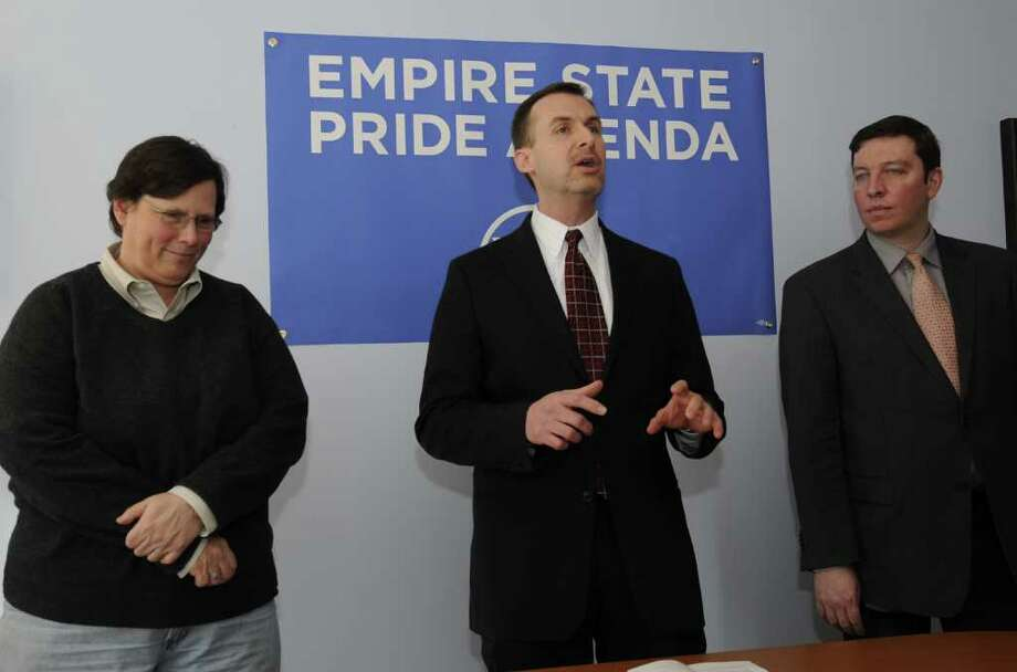 Ross D. Levi, Executive Director of the Pride Agenda, center, flanked by advocate Libby Post, left and Brian Coffin, Pride Agenda's Director of Legislative and Political Affairs, right speaks about their objection to the nomination of Tom Marcelle to the position of Albany County Attorney at their offices in Albany, N.Y. Jan. 31, 2012.  ( Skip Dickstein/Times Union) Photo: Skip Dickstein / 00016280A