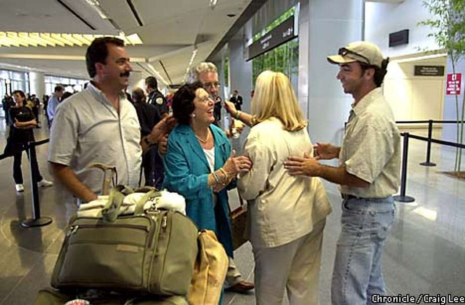 SFO opened back up after security lockdown at San Francisco International Airport due to three planes bombing and hitting the World Trade Center buildings in New York City and the Pentagon on September 11, 2001. Photo of Olimpia (cq) Bragato (woman with glasses) and her daughter, Nancy Bragato (back to camera) being greeted by their family members, Larry Bragato (Olimpia's son, far left) Gary Bragato, (another son behind his mom) and Rick Weil (Nancy's son and Olimpia's grandson). Olimpia and Nancy were in Italy on vacation for a month when their Alitalia flight was diverted to Calgary. Nancy's husband not in the photo, Armando Maraschin, was also on the trip. He was just out of the frame of the photo.  Photo by Craig Lee/San Francisco Chronicle Photo: CRAIG LEE