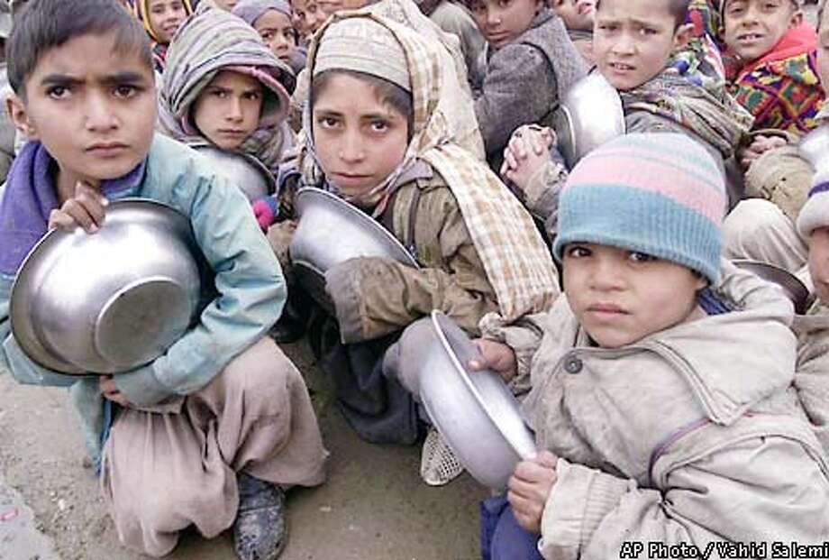 Afghan refugee boys hold plates and crouch in line to receive foods at the Maslakh refugee camp, 12.5 miles (20 kilometers) west of the city of Herat, western Afghanistan, Saturday, Jan. 12, 2002. (AP Photo/Vahid Salemi) Photo: VAHID SALEMI