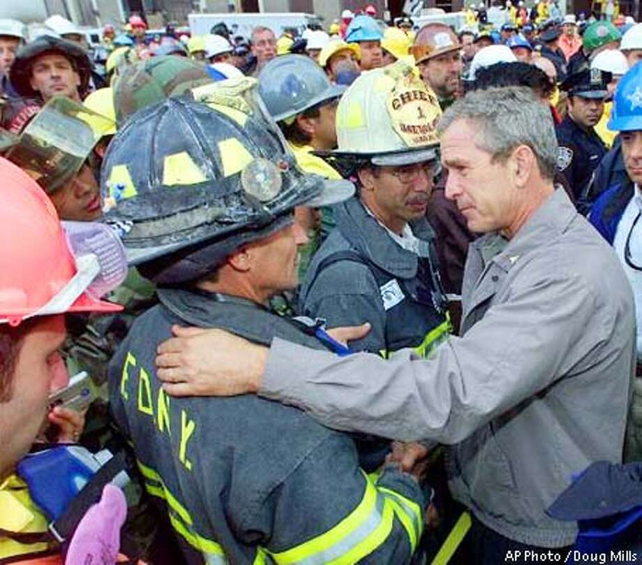 As rescue efforts continue in the rubble of the World Trade Center, President Bush greets fire fighters at the site during a tour of the devastation, Friday, September 14, 2001. Bush is standing on a burned fire truck. Bush toured the disaster site on foot after getting a helicopter view of the devastation. More than 4,700 people remain missing in the devastation of the World Trade Center. (AP Photo / Doug Mills)