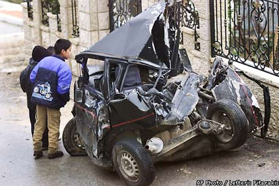 Palestinian boys look at a car destroyed by Israeli army military vehicles during their incursion into the West Bank village of Artas, south of Bethlehem Tuesday Jan. 29, 2002. Israeli troops backed by a tank raided Artas early Tuesday, arresting three Palestinian militants, and withdrawing afterwards. Six Palestinians were wounded in the incursion. (AP Photo/Lefteris Pitarakis) Photo: LEFTERIS PITARAKIS