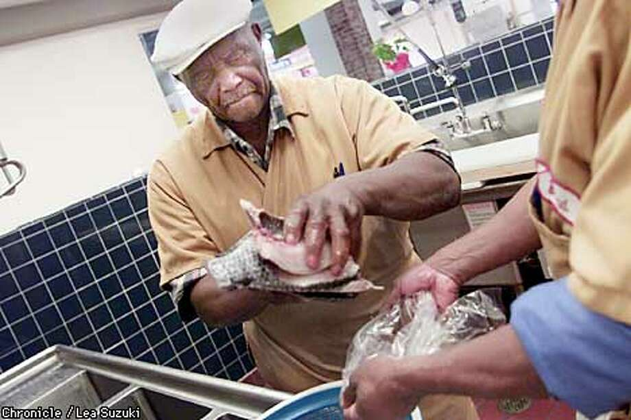 Abe Abraham packages up some fish at the Housewives Market with help from his son Brad Abraham (only hands showing). Abraham, former Glober Trotter, has been selling fish in Oakland for 62 years. He's 78 and still going strong.  Photo by Lea Suzukid/SAN FRANCISCO CHRONICLE Photo: LEA SUZUKI