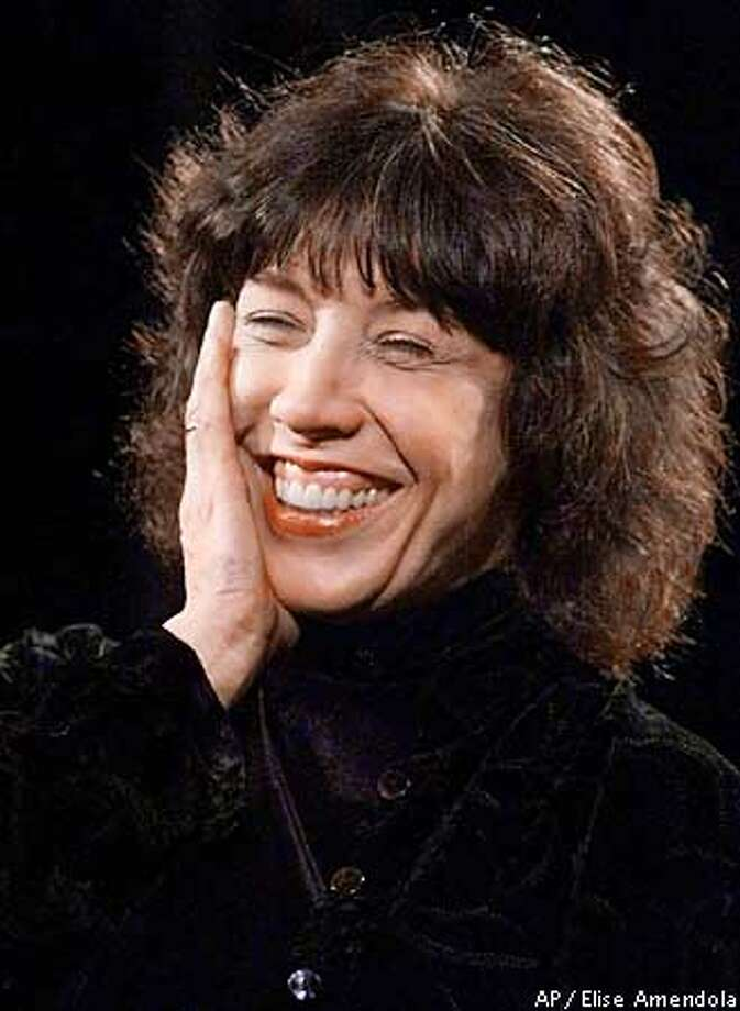 """FILE--Comedian Lily Tomlin smiles as she performs in Boston in this Nov. 16, 1999 file photo. Tomlin is back in New York for a revival of her 1985 one-woman show, """"The Search for Signs of Intelligent Life in the Universe,"""" and is not too thrilled about apartment hunting. """"I wish I lived on a farm,'' Tomlin tells Us Weekly in the Jan. 22 issue, which hits newsstands Friday. """"Too bad we can't have our apartment in New York but (also) have a henhouse and go collect eggs. (AP Photo/Elise Amendola, File) Photo: ELISE AMENDOLA"""