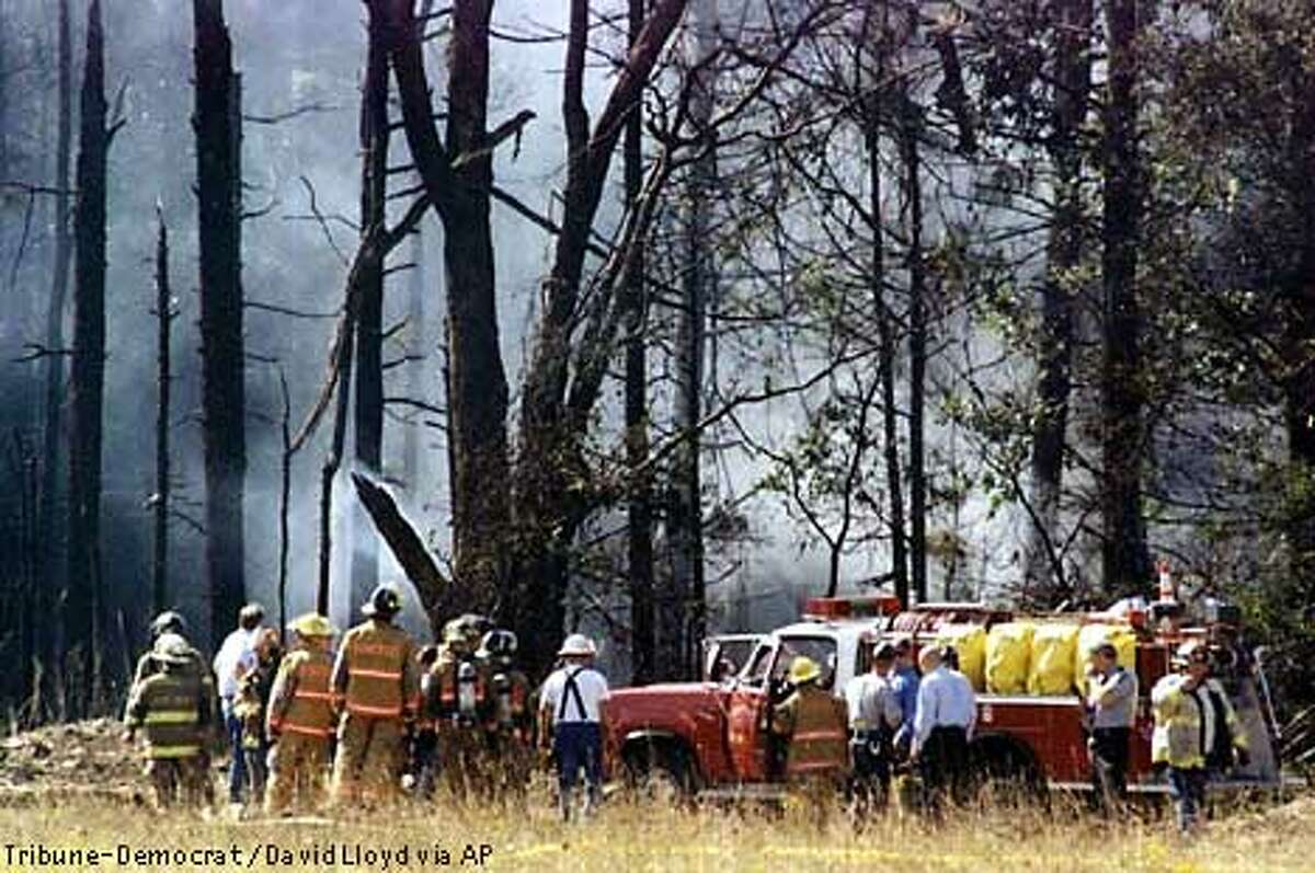 Firefighters and emergency personnel investigate the scene of the crash of a a United Airlines Boeing 757 with at least 45 passengers Tuesday morning, Sept. 11, 2001 near Shanksville, Pa., Somerset County. Radar showed the San Francisco-bound Boeing 757 from Newark, N.J., had nearly reached Cleveland when it made a sharp left turn and headed back toward Pennsylvania, crashing in a grassy field edged by woods about 80 miles southeast of Pittsburgh (AP Photo/Tribune-Democrat/David Lloyd)