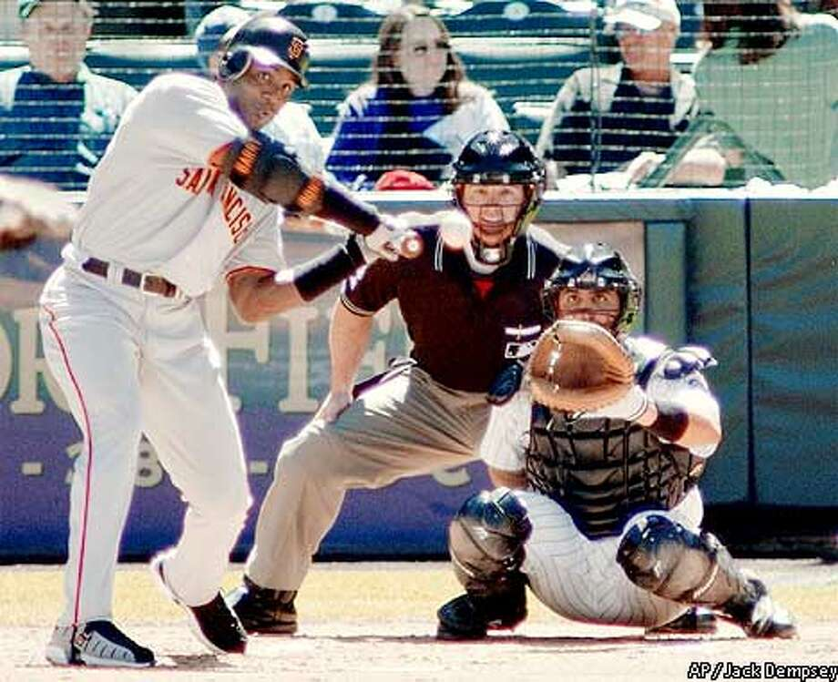San Francisco Giants' Barry Bonds, left, swings as he hits his 61st home run of the season off of Colorado Rockies pitcher Scott Elarton in the firstat Coors Field in Denver on Sunday, Sept. 9, 2001. Catching for the Rockies is Sal Fasano and the home plate umpire is Rob Drake. (AP Photo/Jack Dempsey) Photo: JACK DEMPSEY