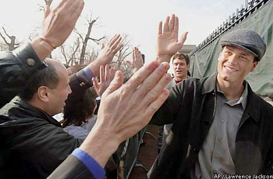New England Patriots quarterbacks Tom Brady, right, and Drew Bledsoe, backround right, take high fives from the fans gathered outside the Statehouse in Boston Monday, Jan. 28, 2002. Acting Gov. Jane Swift threw a pep rally after the Patriots won the AFC title Sunday in Pittsburgh.(AP Photo/Lawrence Jackson) Photo: LAWRENCE JACKSON