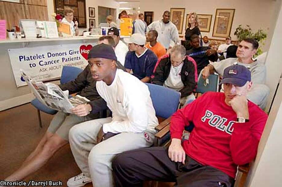 49ers' players Anthony Parker, left (white shirt) and Jeff Garcia, front right, as well as other team members in background watch TV coverage of the tragedy of recent terrorist attacks, as they wait to give blood in the lobby of Pacific Blood Centers in Burlingame. The entire 49er team gave blood at the center in part to help rescue efforts of Americans harmed in recent terrorist attacks. Chronicle Photo by Darryl Bush Photo: Darryl Bush