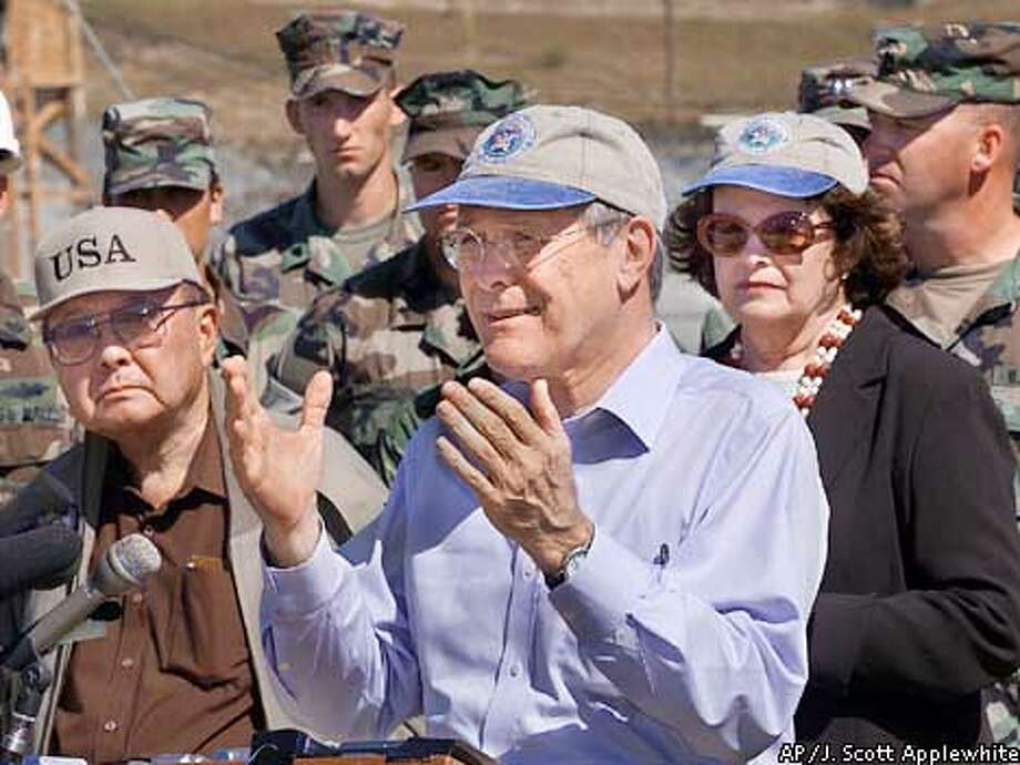 U.S. Secretary of Defense Donald H. Rumsfeld speaks to reporters after a visit to Camp X-Ray, where al-Qaida and Taliban prisoners are being held, at the U.S. Naval Base at Guantanamo Bay, Cuba, Sunday, Jan. 27, 2002. Joining Rumsfeld on his tour are Sen. Dianne Feinstein, D-Calif., at right and Sen. Daniel Inouye, D-Hawaii, at left. (AP Photo/J. Scott Applewhite, Pool) Photo: J. SCOTT APPLEWHITE