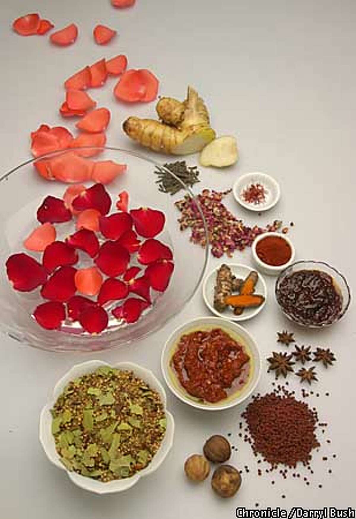 A bowl of rose water and rose petals is surrounded by exotic spices, from top to bottom: galanga root, long pepper (green), saffron (bowl), dried rose petals (left of saffron), pimenton de la vera (red in bowl), fresh turmeric (white bowl), nam prik pao (clear bowl), star anise (star shaped), herissa (bowl left of star anise), achiote (pebble shaped), garam masala (large white bowl), dried oranges (bottom center). Chronicle Photo by Darryl Bush Food Styling by Noel Advincula