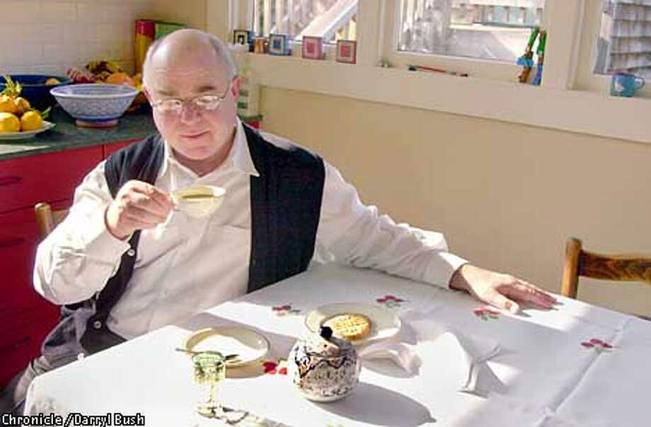 Chef Michael Wild of Bay Wolf, enjoys a special pleasure in the kitchen of his Berkeley home, as he sips from his mother's china and uses his mother's teapot, over his aunt's hand-embroidered table cloth, and grandmother's hand- embroidered napkins. Even the peanut butter cookies have special meaning; made by his wife just the way Mom used to make. Chronicle Photo by Darryl Bush Photo: Darryl Bush
