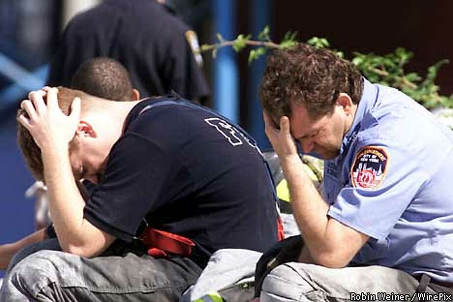 Unidentified firefighters from the New York 48 Engine division react after their search and rescue mission of the World Trade Center scene, Wednesday, Sept. 12, 2001. (Robin Weiner/WirePix for the SF Chronicle) Photo: ROBIN WEINER/WIREPIX