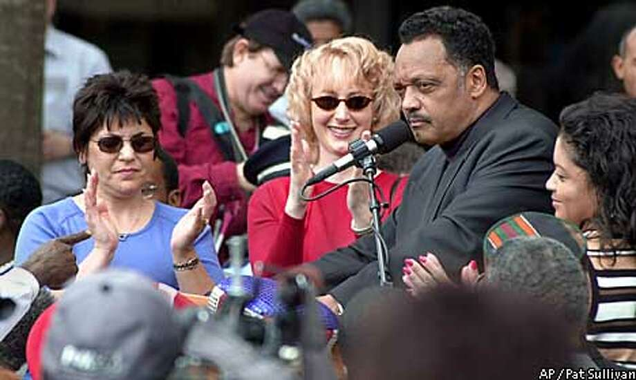 Flanked by former Enron employees Debbie Perrotta, left, Katherine Benedict and Monique Shankle, right, the Rev. Jesse Jackson speaks during a rally in downtown Houston Monday, Jan. 28, 2002. They then boarded a bus to head to Washington D.C. where Jackson and his supporters will petition the federal government for legislation to help former Enron workers. (AP Photo/Pat Sullivan) Photo: PAT SULLIVAN