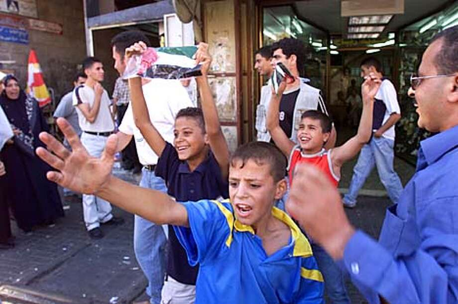 A group of children near east Jerusalem's Old City wave Palestinian flags and chant anti-U.S slogans as they react to the news of a terrorist attack on the World Trade Center in New York Tuesday Sept. 11, 2001. (AP Photo/Lefteris Pitarakis) Photo: LEFTERIS PITARAKIS