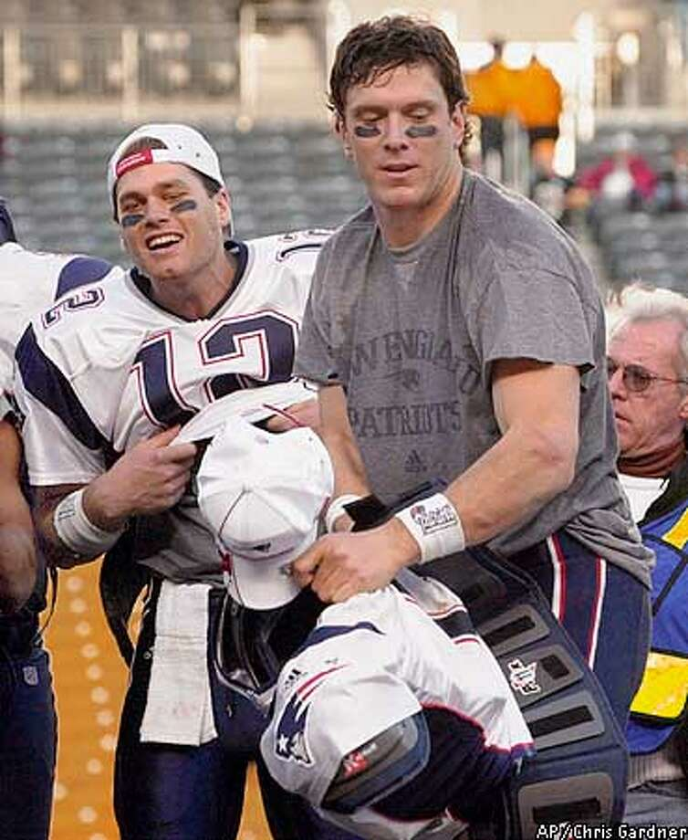 New England Patriots quarterbacks Tom Brady (12) and Drew Bledsoe get ready for the trophy presentation after the Patriots beat the Pittsburgh Steelers in the game Sunday, Jan. 27, 2002, in Pittsburgh. Bledsoe took over after Brady was injured in the first half. (AP Photo/Chris Gardner) Photo: CHRIS GARDNER