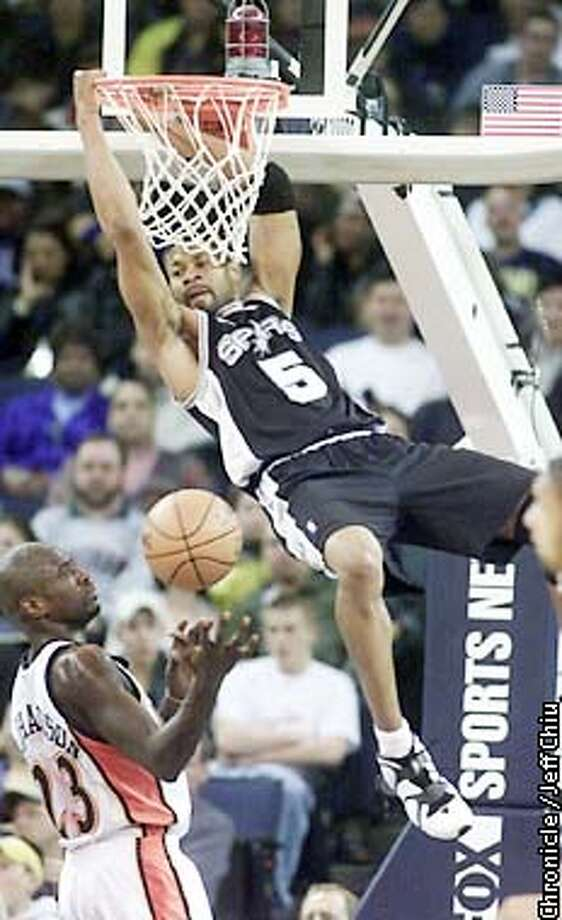 The Spurs' Charles Smith hangs on the rim after dunking over Jason Richardson of the Warriors in the first quarter as the Warriors host the San Antonio Spurs in Oakland on Saturday night. Photo by Jeff Chiu / The Chronicle. Photo: Jeff Chiu