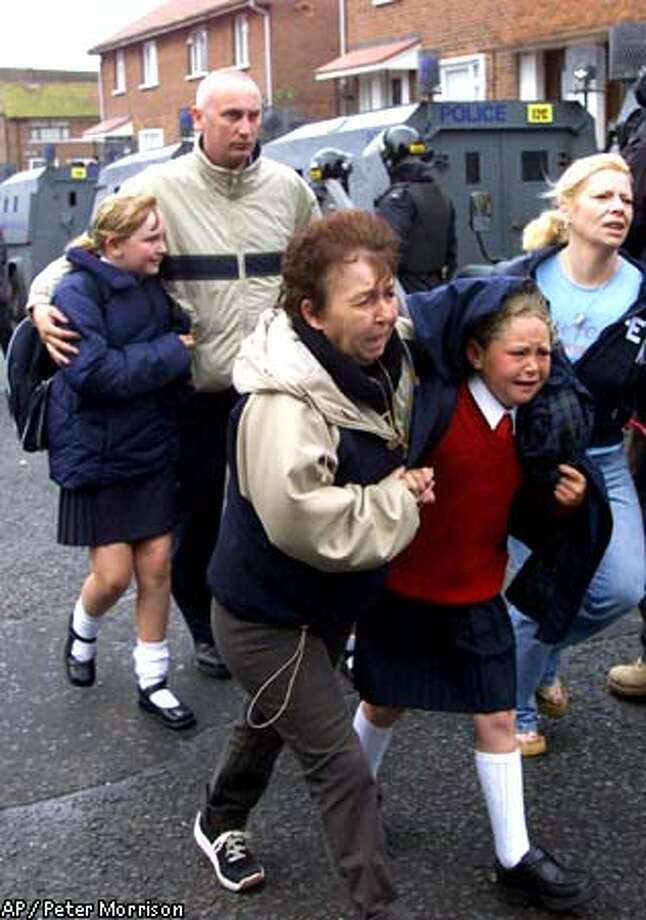 Roman Catholic school girls and their parents make their way through a Protestant area to Holy Cross Roman Catholic school in north Belfast, Wednesday, Sept. 5, 2001. The Catholic children came under attack from shouting and stone-throwing Protestant protesters for the third day as they made their way to school. (AP Photo/Peter Morrison) Photo: PETER MORRISON
