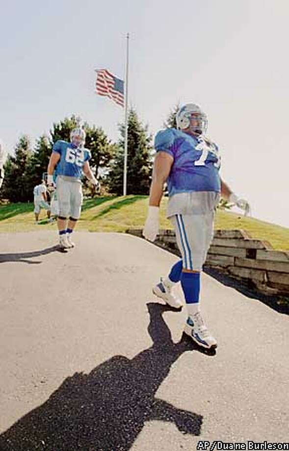 With the American Flag at half-staff, the Detroit ' Aaron Gibson (71) and Tony Semple (62) leave their afternoon practice at the Silverdome Wednesday, Sept. 12, 2001, in Pontiac, Mich. The NFL has not yet decided whether to play games this weekend. (AP Photo/Duane Burleson) Photo: DUANE BURLESON