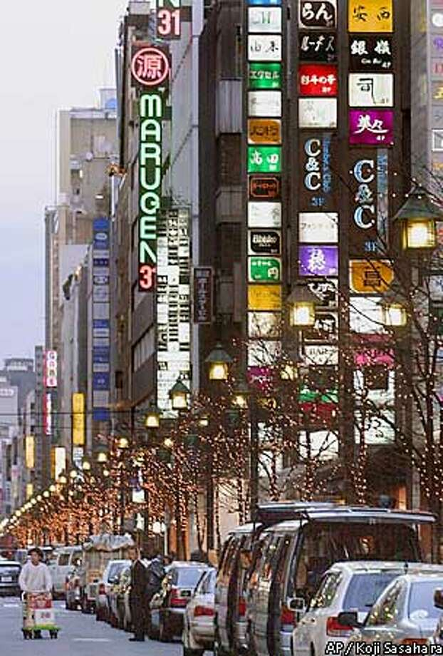 Neon signs advertising bars and clubs are turned on as the sun goes down along Namiki-dori Avenue in the Ginza district, one of Tokyo's most posh nightlife centers, Friday, Jan. 14, 2000. Making deals and solidifying personal connections at exclusive and expensive clubs has long been the way serious business is done in Japan. But after a very bad decade for the economy and an influence-buying scandal that cast the wining-and-dining tradition in a less-forgiving light, companies are becoming downright cheap with their expense accounts. (AP Photo/Koji Sasahara) Photo: KOJI SASAHARA