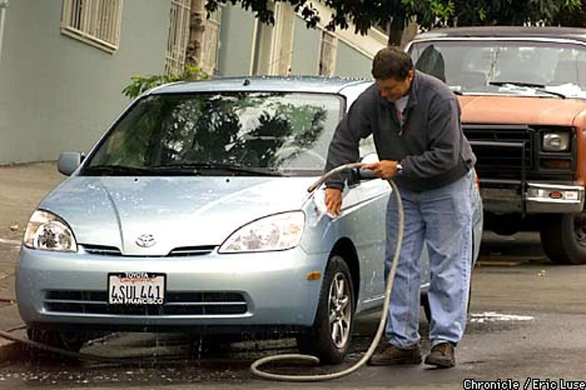 Otis Maxwell washes his wifes car, a hybrid Toyota that is a cross between electric and combustion. BY ERIC LUSE/THE CHRONICLE