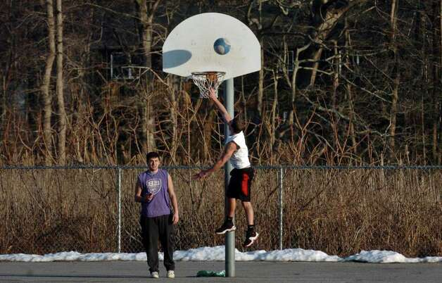 Ricky Festa, of Milford, lays up the basketball as his buddy Dan Altieri, also from Milford, looks on, as they enjoy the mild weather at Calf Pen Meadow School in Milford, Conn. on Tuesday January 31, 2012. Photo: Christian Abraham / Connecticut Post