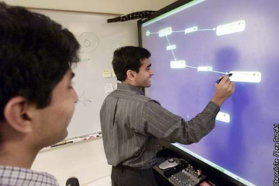 """From left: Naveen Sastry and Anoop Sinha. Sinha demonstrates his previous project, """"Suede"""" at the Human Centered Computing Lab in Soda Hall at UC Berkeley as Naveen Sastry looks on. Computer science grad students lured away by dot-com riches are now returning to school. Naveen Sastry started back again at UC Berkeley last fall, after working at a financial software firm at the tail end of the tech boom. His friend and classmate Anoop Sinha, never left. Photo by Lea Suzuki/SAN FRANCISCO CHRONICLE Photo: LEA SUZUKI"""