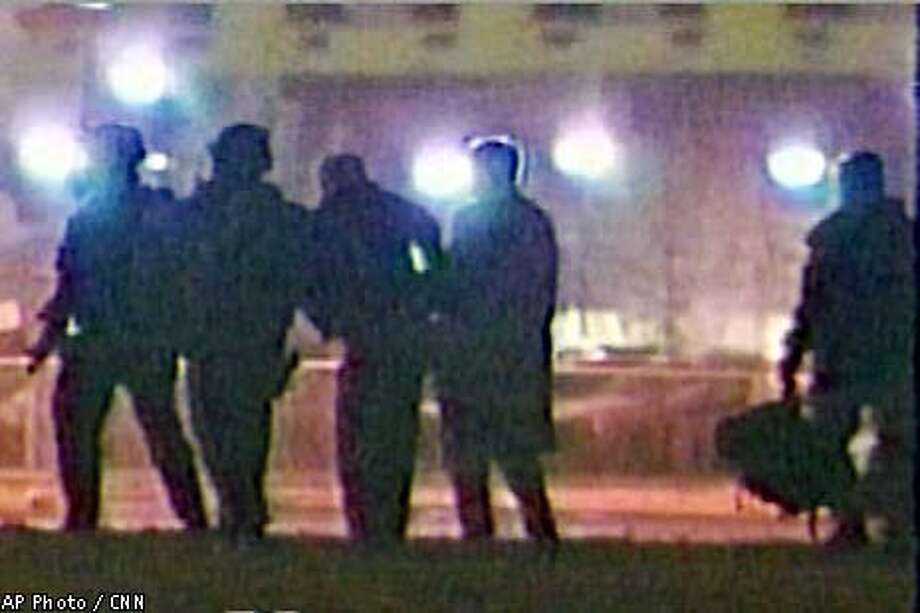 John Walker Lindh, third from left, is seen being escorted by federal agents near the federal courthouse in Alexandria, Va., in this image from television, Wednesday, Jan. 23, 2002. Lindh, the young Muslim convert accused of joining al-Qaida soldiers in Afghanistan, returned to the United States Wednesday under FBI custody to face criminal charges that he conspired to kill fellow Americans. (AP Photo/CNN)