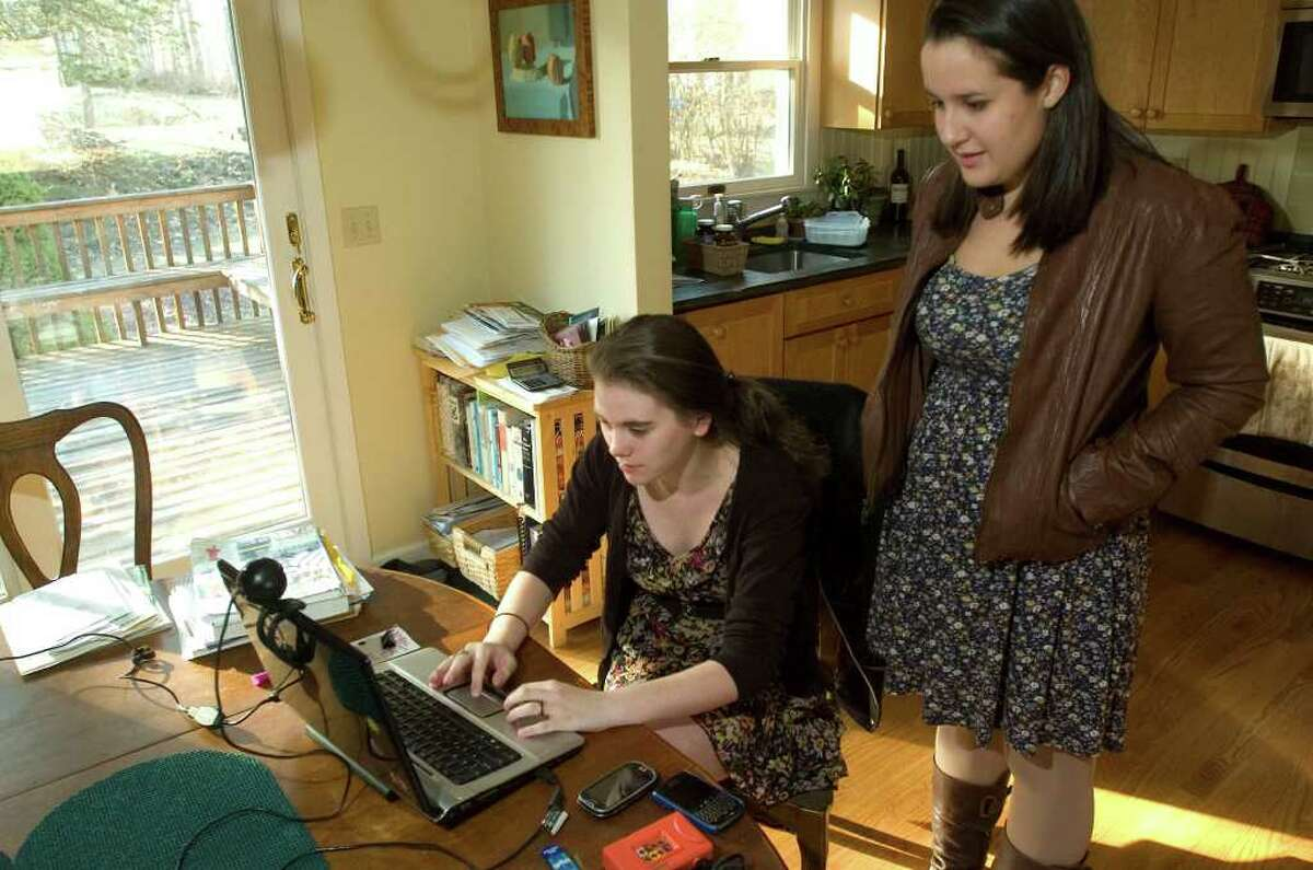 Sophie Needleman, 18, seated, and Kelly Aaronson, 17, check their Facebook page