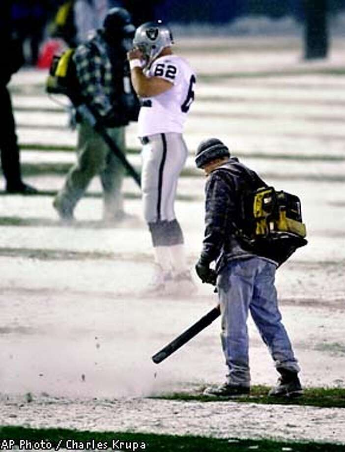 Stadium workers use leaf blowers to clear snow off the yardage stripes as Oakland Raiders center Adam Treu (62) checks out the field prior to their AFC Divisional Playoff game against the New England Patriots at Foxboro Stadium, in Foxboro, Mass., Saturday Jan. 19, 2002. (AP Photo/Charles Krupa) Photo: CHARLES KRUPA