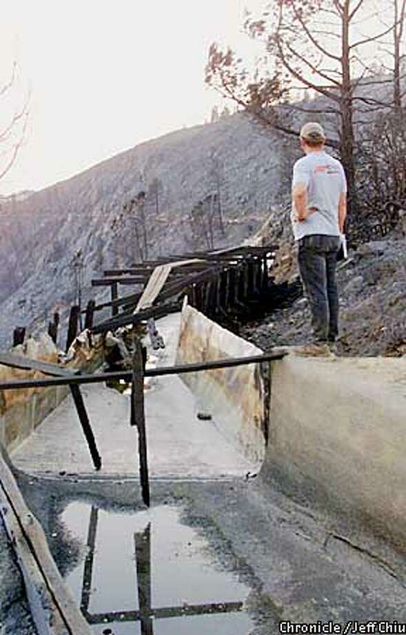 Vern Pyle, general manager of Utica Power, overlooks the damage of the nearly 100-year-old 3-quarter mile flume caused by the Darby wildfire, which burned down the 3-quarter mile flume on Thursday, on Saturday afternoon just outside of Murphy's Camp. The loss of the flume has caused residents from Angels Camp to Murphy's Camp in Calaveras County to be without water, while about 397 homes in 9 communities, including Hathaway Pines and Forest Meadows, were evacuated because of the fire. Photo by Jeff Chiu / The Chronicle. Photo: Jeff Chiu