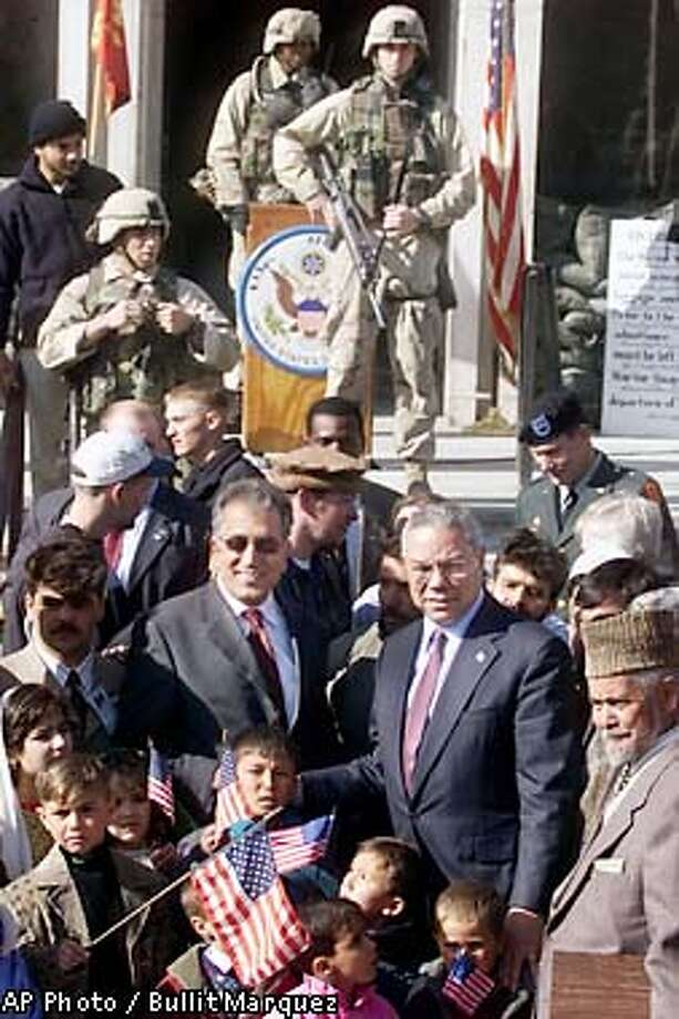 U.S. Secretary of State Collin Powell, center right, and U.S. presidential envoy to Afghanistan Zalmay Khalilzad, center left, pose for a photo at the U.S. Embassy in Kabul, Thursday, Jan. 17, 2002 . Bottom right is Nawab Ali, a long-time employee of the U.S embassy in Kabul whose award as 1996 best foreign service personnel was taken away and destroyed by the Taliban. (AP Photo/Bullit Marquez) Photo: BULLIT MARQUEZ