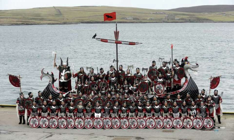 Participants dressed as Vikings pose beside their longboat during the annual Up Helly Aa festival in